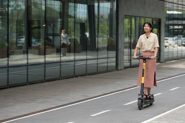 Volledig geschoten smileyvrouw met scooter