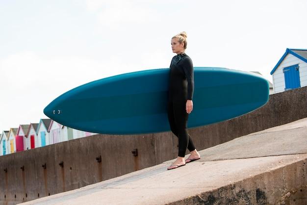 Volledig geschoten sportieve vrouw die paddleboard draagt