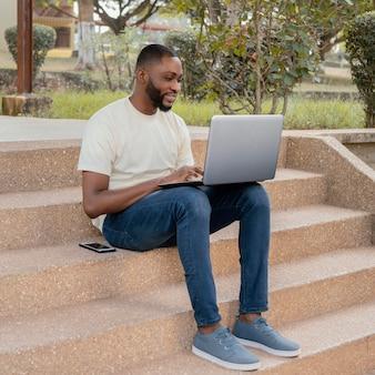 Volledig geschoten student op trappen met laptop