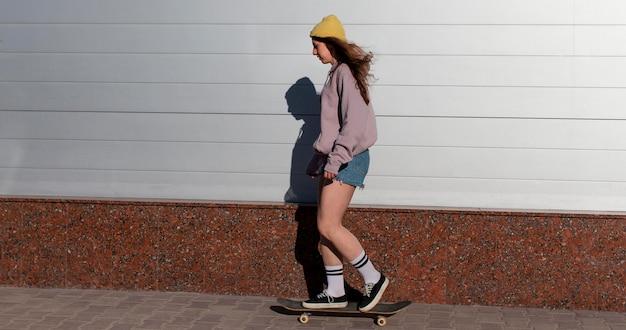 Volledig geschoten tienermeisje die buiten schaatsen