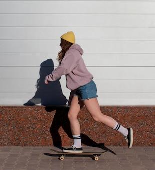 Volledig geschoten tienermeisje die in openlucht schaatsen