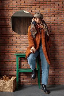 Volledig geschoten trendy meisje met jas het stellen