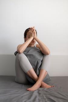 Volledig geschoten trieste vrouw met kussen in bed