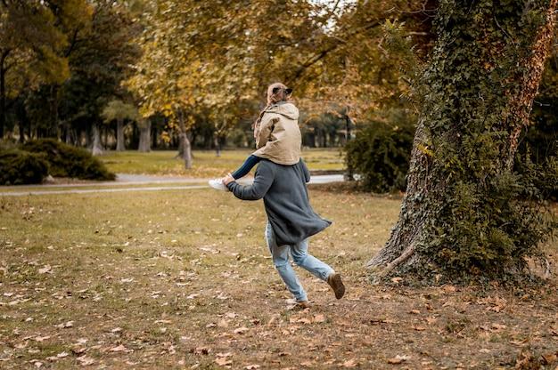 Volledig geschoten vader dragende meisje op schouders