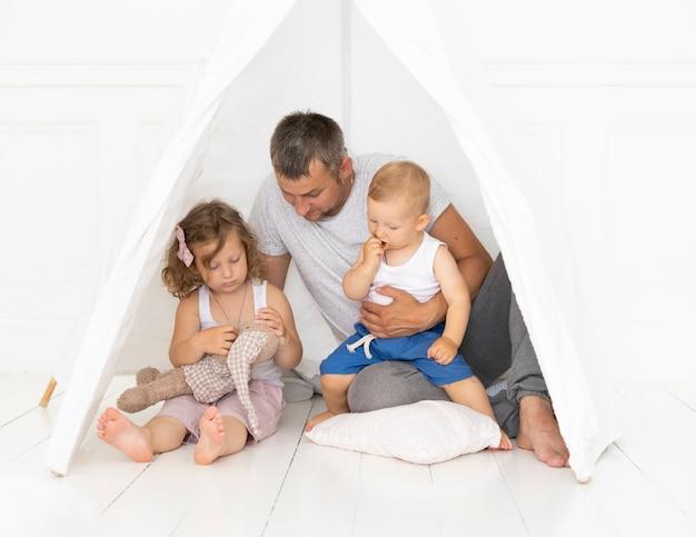 Volledig geschoten vader spelen met zijn kind in een tent