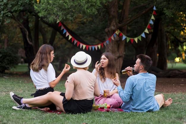 Volledig geschoten vrienden die bij picknick eten