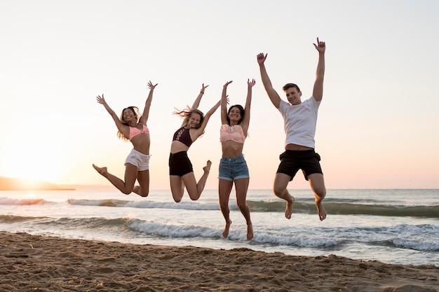Volledig geschoten vrienden die op strand springen