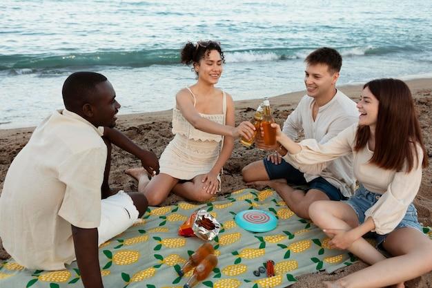 Volledig geschoten vrienden die op strand zitten