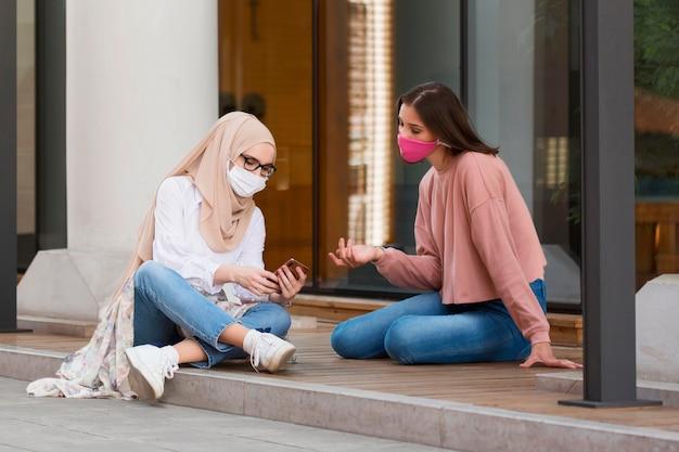 Volledig geschoten vrienden met maskers buitenshuis