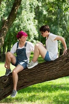 Volledig geschoten vrienden zittend op boomstam