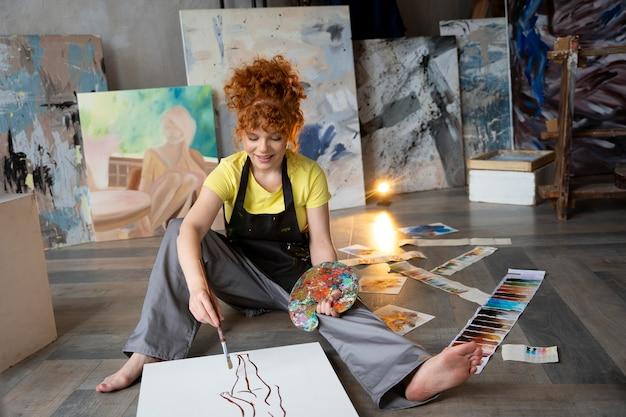 Volledig geschoten vrouw aan het schilderen op de vloer