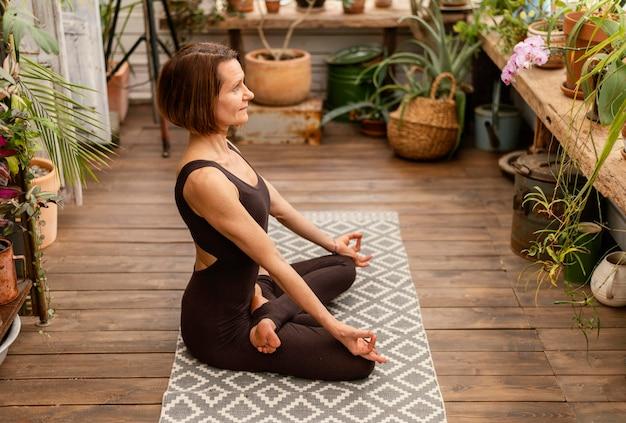 Volledig geschoten vrouw binnenshuis op yogamat