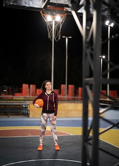 Volledig geschoten vrouw die basketbal buiten houdt