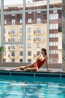 Volledig geschoten vrouw die bij het zwembad zit