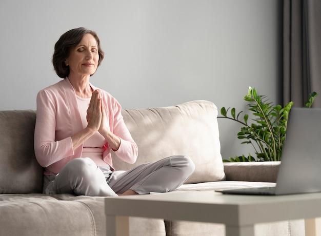 Volledig geschoten vrouw die binnenshuis mediteert