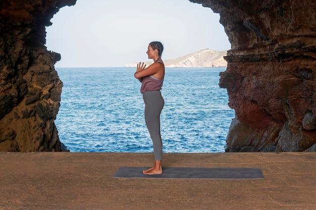 Volledig geschoten vrouw die buiten yoga doet