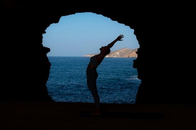 Volledig geschoten vrouw die buiten yoga poseert