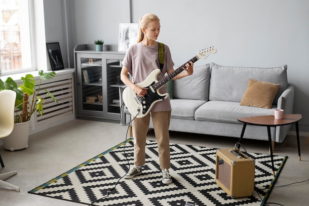 Volledig geschoten vrouw die gitaar speelt