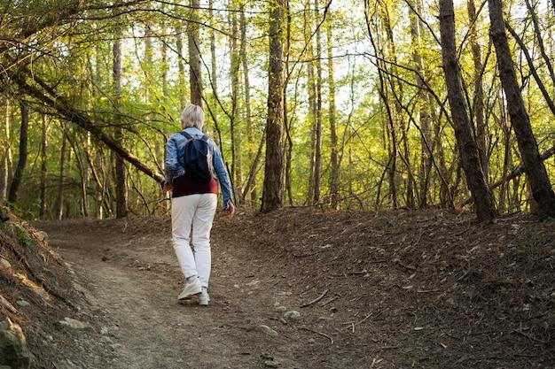 Volledig geschoten vrouw die in het bos loopt