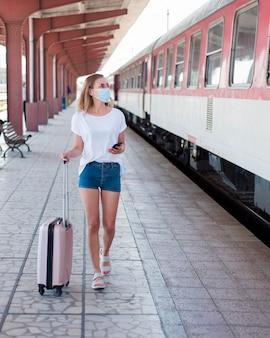 Volledig geschoten vrouw die masker met bagage in treinstation draagt