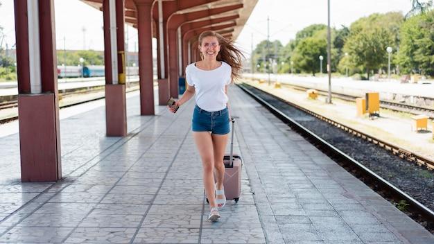 Volledig geschoten vrouw die met bagage in treinstation loopt