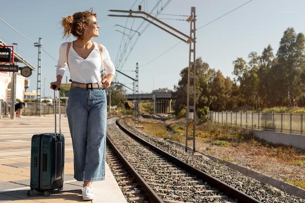 Volledig geschoten vrouw die met bagage reist