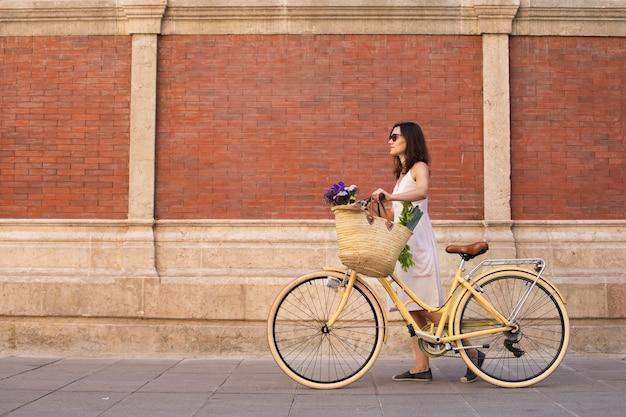 Volledig geschoten vrouw die met fiets loopt