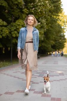 Volledig geschoten vrouw die met hond loopt