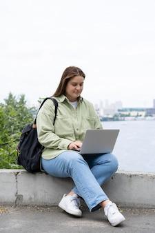 Volledig geschoten vrouw die met laptop zit