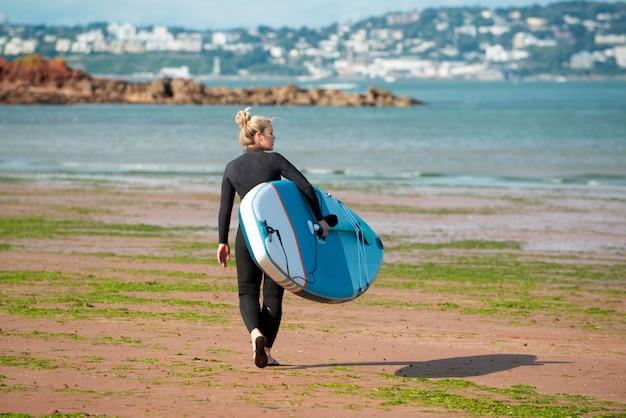 Volledig geschoten vrouw die met paddleboard loopt