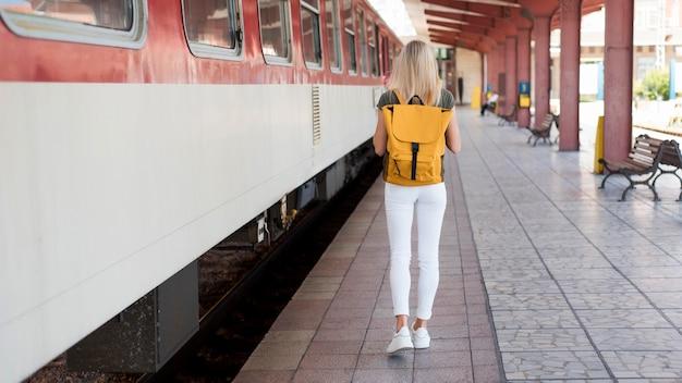 Volledig geschoten vrouw die met rugzak langs trein loopt