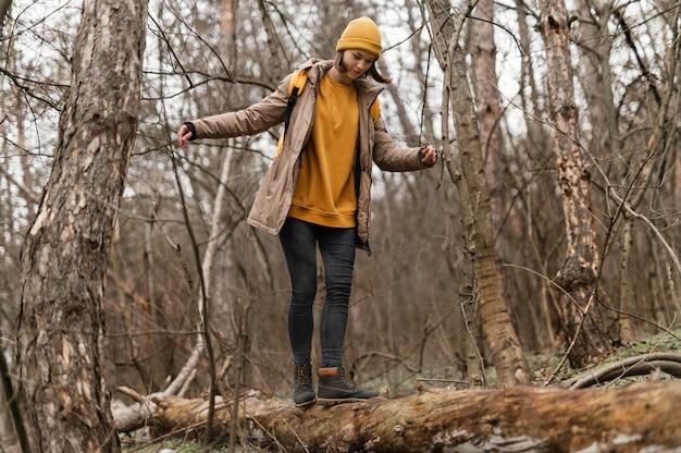 Volledig geschoten vrouw die op boomtak loopt