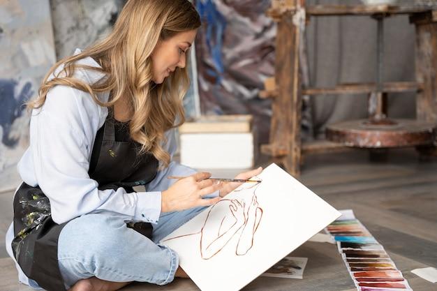 Volledig geschoten vrouw die op canvas schildert