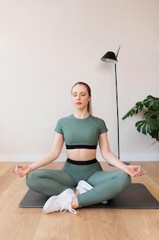 Volledig geschoten vrouw die op mat mediteert