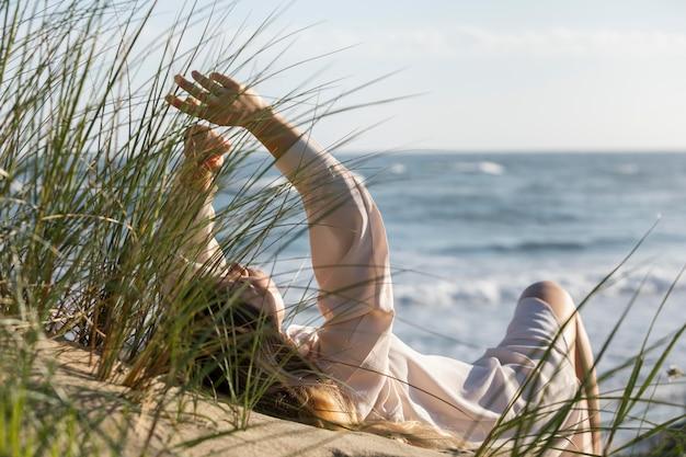 Volledig geschoten vrouw die op strand legt