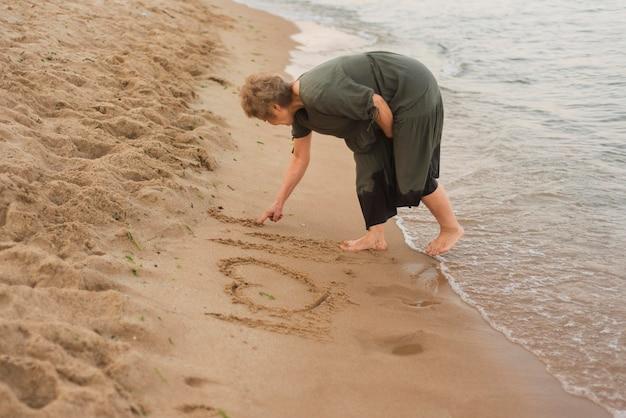 Volledig geschoten vrouw die op zand schrijft