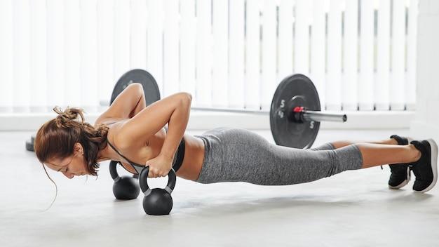 Volledig geschoten vrouw die push-ups doet
