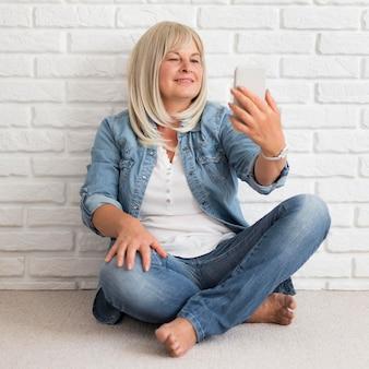 Volledig geschoten vrouw die telefoon bekijkt