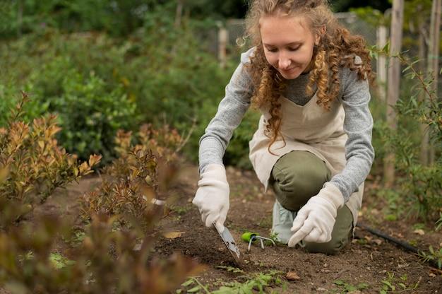 Volledig geschoten vrouw die tuiniert met gereedschap