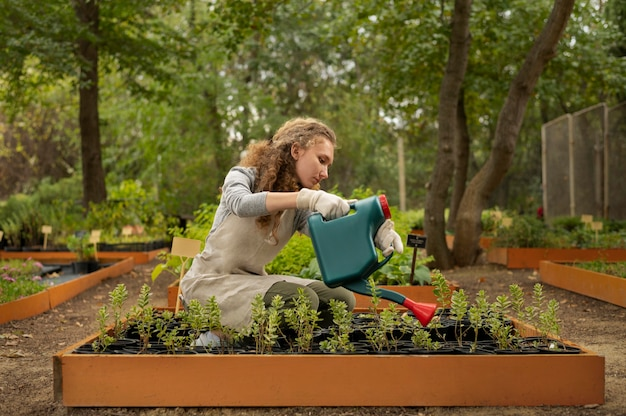 Volledig geschoten vrouw die tuinplanten water geeft