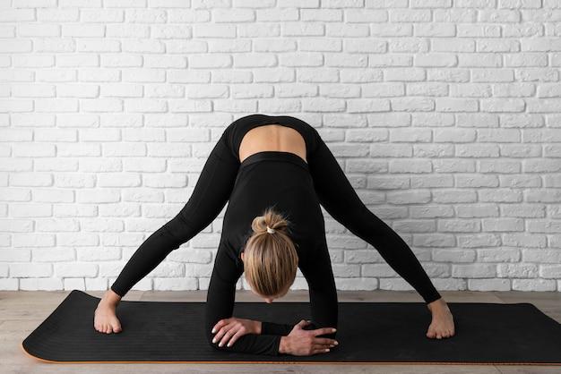 Volledig geschoten vrouw die yoga op mat doet