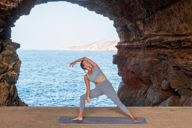 Volledig geschoten vrouw doet yoga pose aan zee