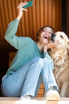 Volledig geschoten vrouw en hond die selfie nemen