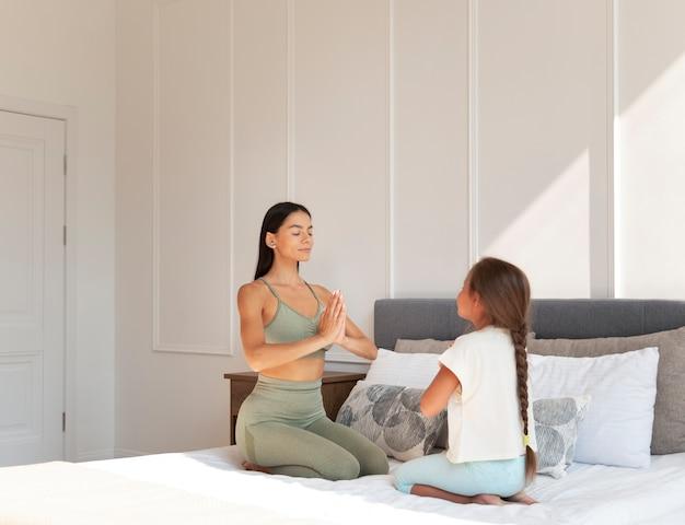 Volledig geschoten vrouw en kind mediteren in bed
