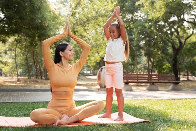 Volledig geschoten vrouw en meisje die yoga doen