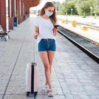 Volledig geschoten vrouw met bagage in treinstation