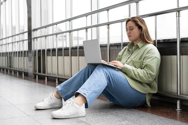 Volledig geschoten vrouw met laptop