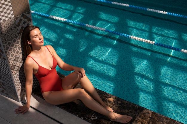 Volledig geschoten vrouw ontspannen bij het zwembad