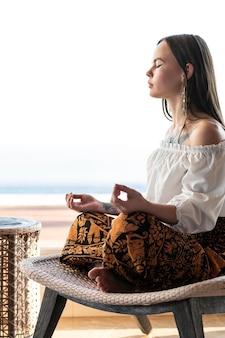 Volledig geschoten vrouw op stoel mediteren