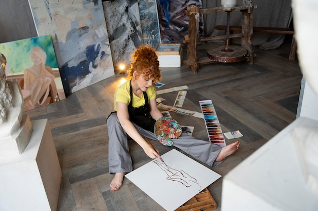 Volledig geschoten vrouw op vloer schilderen met penseel Gratis Foto
